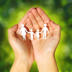 Paper Family in Hands over Green Sunny Background. Family